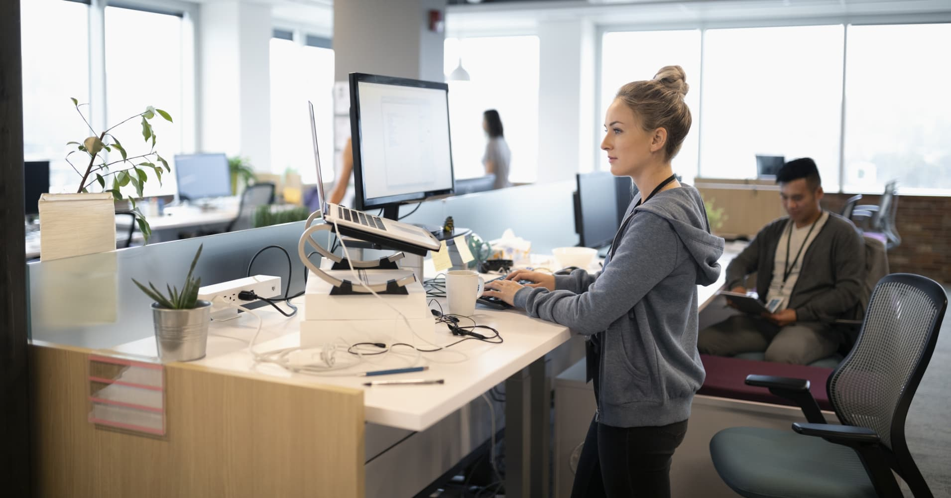 Creative businesswoman standing at desk, using laptop and computer in open plan office