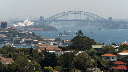 Residential buildings and houses stand as the Sydney Harbour Bridge and Sydney Opera House stand in the background in Sydney, Australia, on Saturday, Jan. 12, 2019.