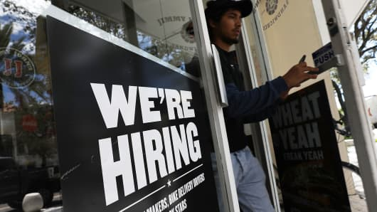 A 'We're hiring' sign is seen in a restaurant window on September 7, 2018 in Miami, Florida.
