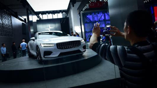 A man uses his mobile phone to take a picture of a Polestar 1 car at the Beijing auto show on April 26, 2018. -