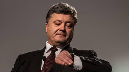 Incumbent Ukrainian President Petro Poroshenko checks his watch as he speaks to the media.