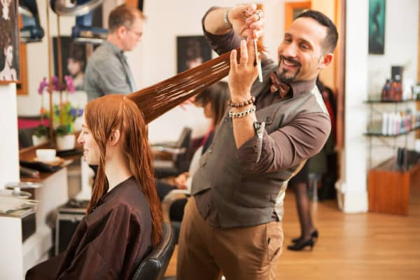 Female customer having long red hair trimmed in hair salon