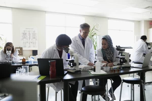 Professor helping students conducting scientific experiment in laboratory