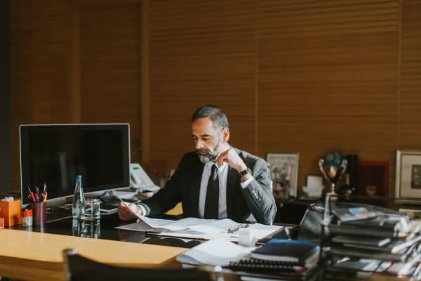 Senior businessman working on laptop in modern office