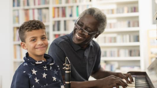 Portrait smiling, confident grandfather and grandson playing piano and clarinet