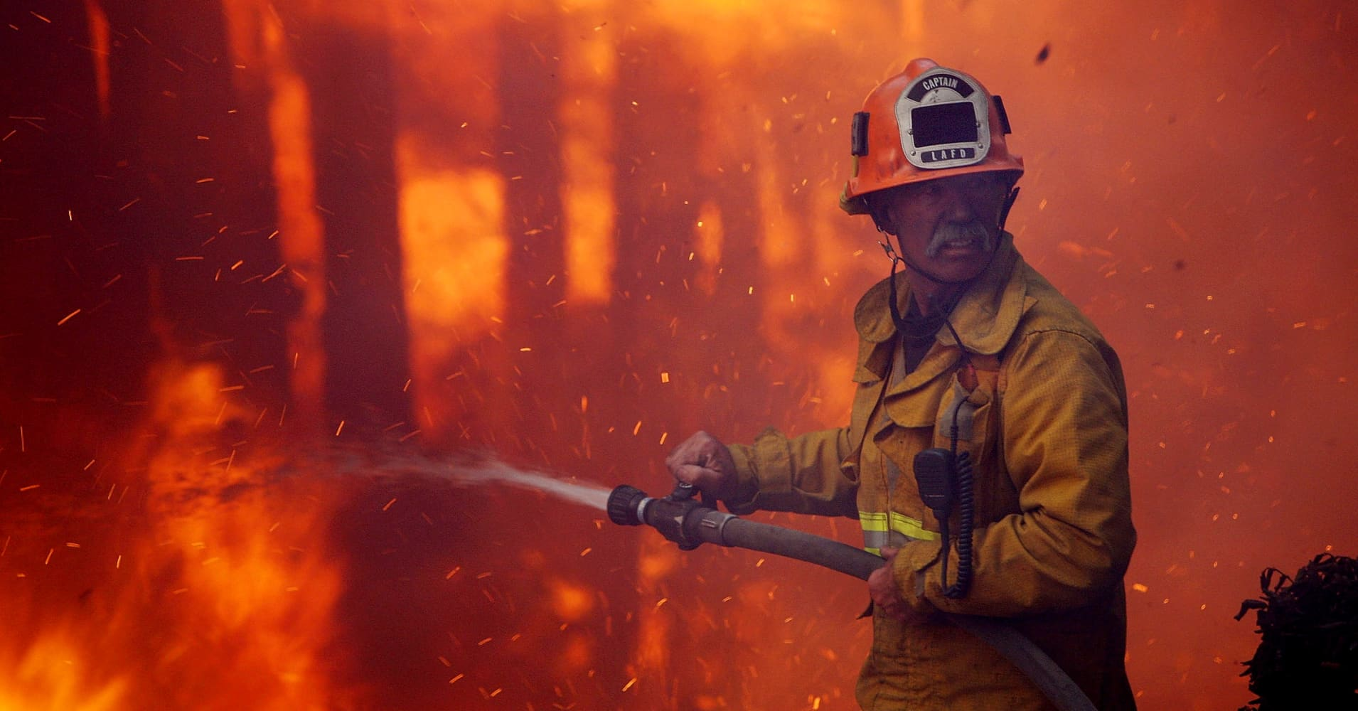 A firefighter calls for water as a mobile home park burns in the Sylmar Fire in Sylmar, California.