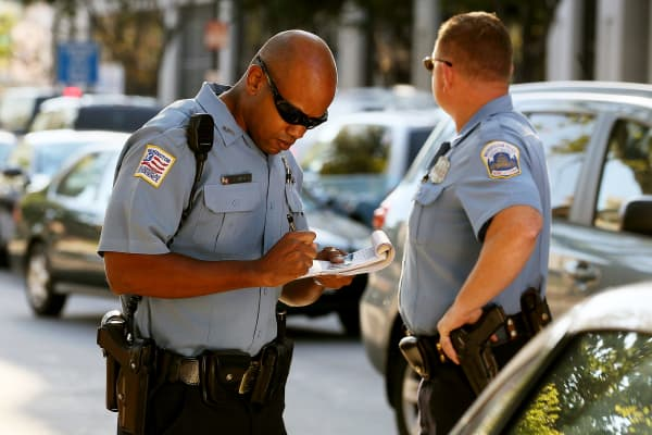 A police officer writes a ticket to a motorist in Washington, D.C.