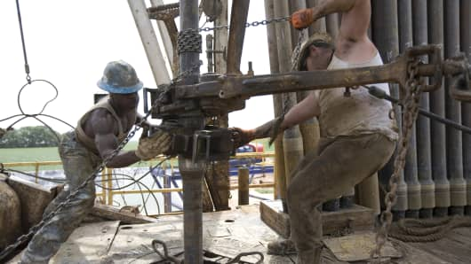 Deck hands tighten sections of steel pipe and insert them back into a well on a natural gas drilling rig outside of Artesia, in eastern New Mexico, which is part of the Permian Basin that extends into the state to the west of Texas.