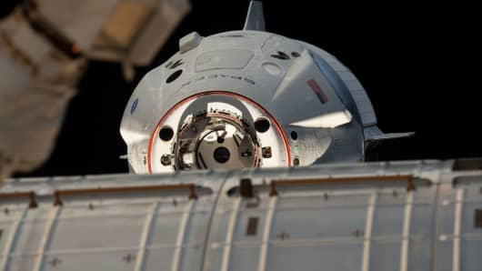 The uncrewed SpaceX Crew Dragon spacecraft at the International Space Station with its nose cone open revealing its docking mechanism while approaching the station.
