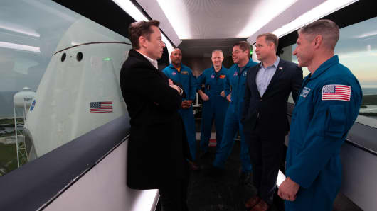 SpaceX founder and CEO Elon Musk speaks with NASA administrator Jim Bridenstine, along with astronauts Victor Glover, Doug Hurley, Bob Behnken and Mike Hopkins, in front of the company's Crew Dragon capsule.
