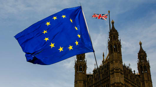 A European Union (EU) flag flies outside the Houses of Parliament in London, U.K., on Thursday, March 7, 2019.