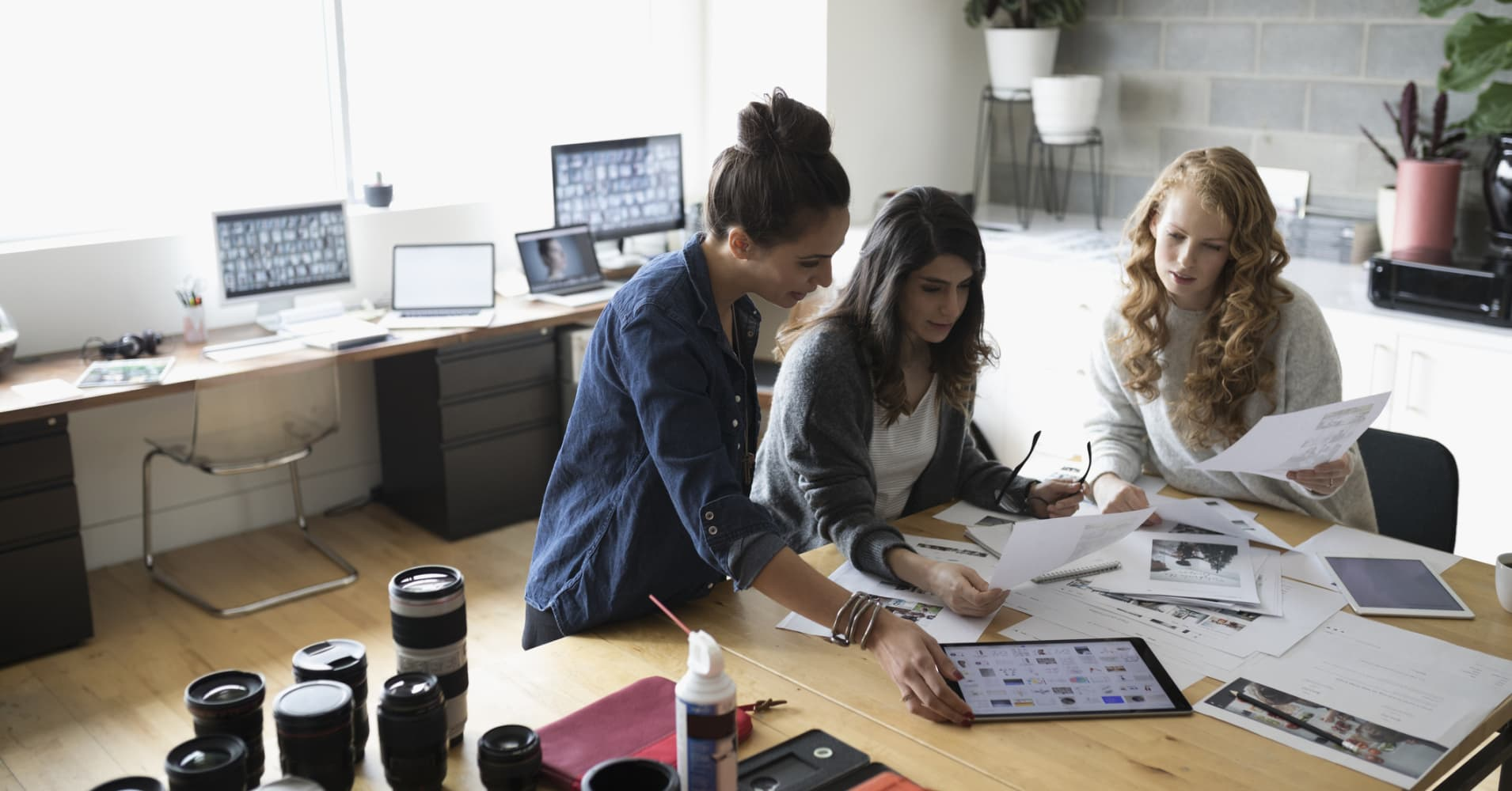 Female photo editors with digital tablet reviewing photo proofs in office