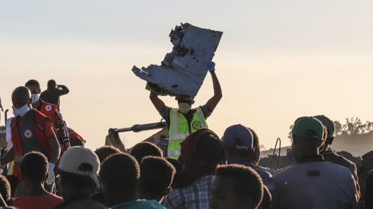 A man carries a piece of debris on his head at the crash site of a Nairobi-bound Ethiopian Airlines flight near Bishoftu, a town some 60 kilometers southeast of Addis Ababa, Ethiopia, on March 10, 2019.