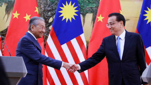 Malaysia's Prime Minister Mahathir Mohamad (left) shakes hands with China's Premier Li Keqiang (right) at the end of their joint press conference at the Great Hall of the People in Beijing on August 20, 2018.