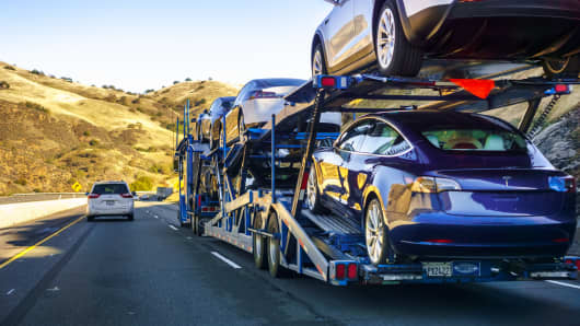 Car transporter carries Tesla Model 3 vehicles along the highway.