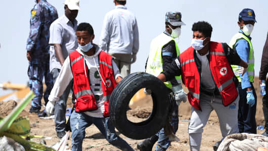 Search workers carry a tyre at the scene of the Ethiopian Airlines Flight ET 302 plane crash, near the town of Bishoftu, southeast of Addis Ababa, Ethiopia March 11, 2019.