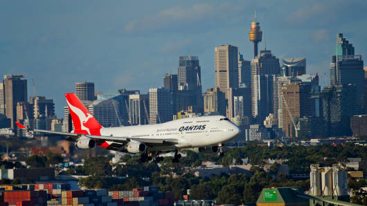 A QANTAS Boeing 747 flies extremely low past buildings and industrial sites on its final approach to the city's airport, in Sydney.