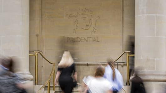 Pedestrians pass a logo outside Prudential Plc's headquarters in London, U.K.