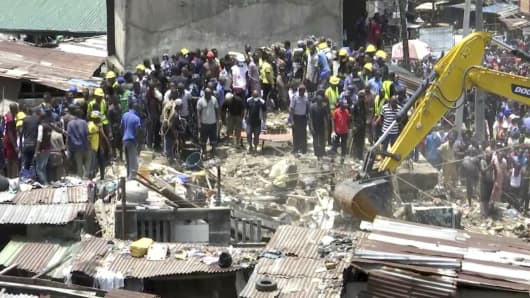 In this image taken from video, rescue workers and emergency teams work at the scene of a building collapse in Lagos, Nigeria, Wednesday March 13, 2019.