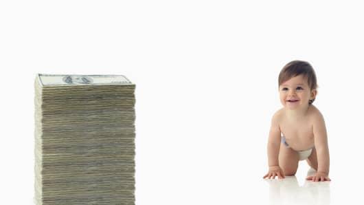 Baby crawling towards pile of money
