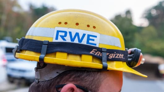 An employee of the energy group RWE stands in the Hambach Forest with a helmet bearing the company's logo. The police and the energy company RWE have started to clear the Hambach Forest.