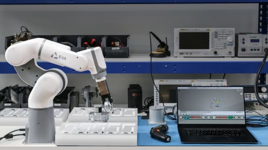 Eva, a robotic arm developed by U.K. start-up Automata Technologies, is perched on a table near a laptop.