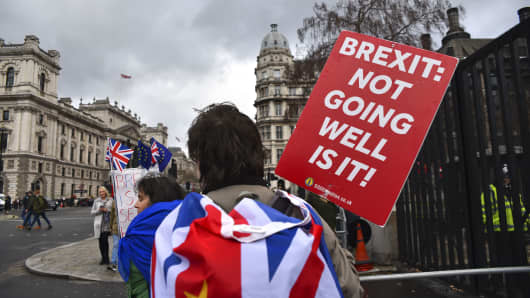 Anti Brexit demonstrators gather outside the Houses of Parliament holding placards, London on March 14, 2019. Prime minister Theresa May will make a third attempt to get her EU withdrawal deal through Parliament in the next week.