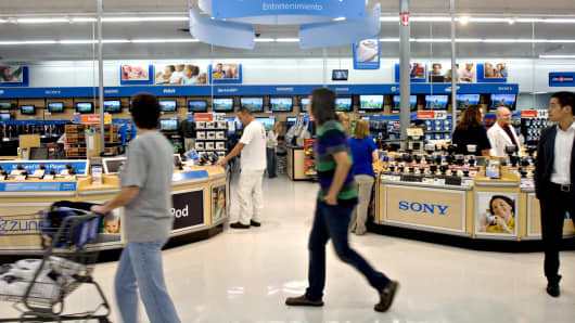 Shoppers walk past the entertainment and electronics section in a Wal-Mart Supercenter store in Rogers, Arkansas.