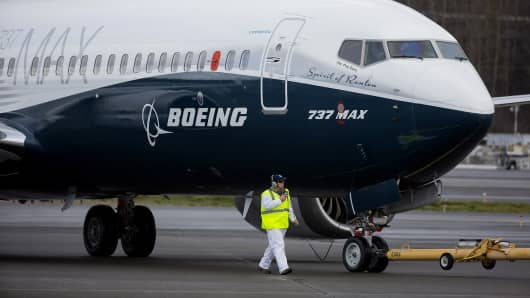 Crewman tow in a Boeing Co. Max 737 jet after landing at King County International Airport in Seattle, Washington, U.S., on Friday, Jan. 29, 2016. Boeing Co.'s newest 737 jetliner gunned its engines and headed into rain-streaked skies Friday, with profit and pride riding on its wings. Photographer: Mike Kane/Bloomberg via Getty Images