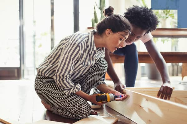 Younger females assembling furniture with energy drill