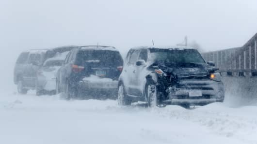 A string of wrecked vehicles sit on an overpass over Interstate 70 as a late winter storm packing hurricane-force winds and snow sweeps over the intermountain West Wednesday, March 13, 2019, in Aurora, Colo.