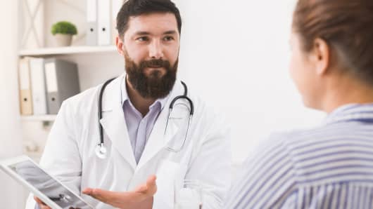Doctor is consulting patient with digital tablet