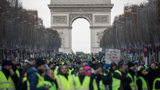 Protesters chant slogans as during the 'yellow vests' demonstration on the Champs-Elysées near the Arc de Triomphe on December 8, 2018 in Paris France.