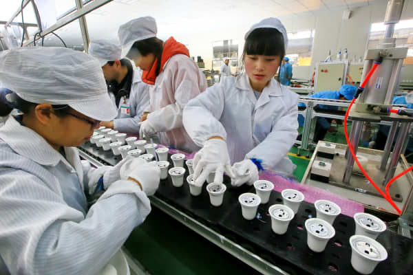 Chinese employees working on an energy-saving bulb production line in Suining, Sichuan province, China.