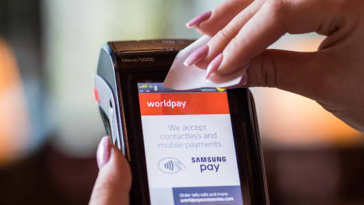 A waitress tears a receipt from a Worldpay Inc. payment terminal at a restaurant in this arranged photograph in London, U.K., on Monday, March 18, 2019. Fidelity National Information Services Inc. agreed to acquire Worldpay Inc. for about $34 billion in cash and stock, the biggest deal ever in the booming international payments sector.
