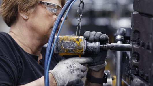 A factory worker uses a power drill to assemble components on a diesel engine at the Cummins Inc. Seymour Engine Plant in Seymour, Indiana, Jan. 29, 2019.