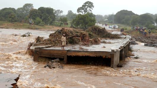 A man looks at a washed away bridge along Umvumvu river following Cyclone Idai in Chimanimani, Zimbabwe March 18, 2019.