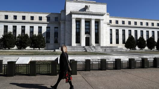 A pedestrian walks past the Federal Reserve building on Constitution Avenue in Washington, March 19, 2019.