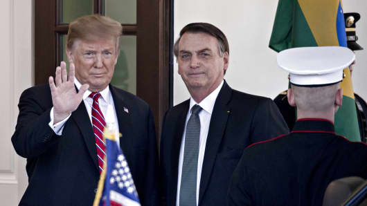 U.S. President Donald Trump, left, waves while standing with Jair Bolsonaro, Brazil's president, at the West Wing of the White House in Washington, D.C., U.S., on Tuesday, March 19, 2019.