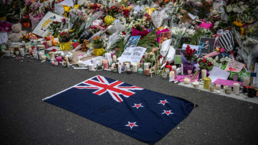 A New Zealand flag is placed next to flowers and tributes near Al Noor mosque on March 18, 2019 in Christchurch, New Zealand. 50 people were killed, and dozens are still injured in hospital after a gunman opened fire on two Christchurch mosques on Friday, 15 March.