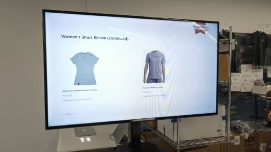 "A screen in Tesla's Gigafactory advertising ""Merch Madness,"" a chance for employees to buy discounted company swag."