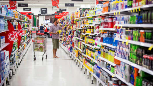 A shopper selects produts in an aisle inside a Coles supermarket, operated by Wesfarmers Ltd., in Sydney, Australia, on Tuesday, Feb. 18, 2014.