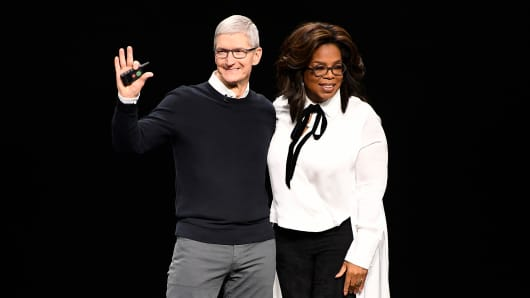 Tim Cook, chief executive officer of Apple Inc., waves while onstage with Oprah Winfrey, chief executive officer of Oprah Winfrey Network LLC, during an event at the Steve Jobs Theater in Cupertino, California, U.S., on Monday, March 25, 2019.
