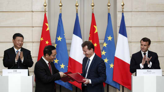 French President Emmanuel Macron (R) and Chinese President Xi Jinping (L) applaud as President of Airbus's commercial aircraft business Guillaume Faury (2ndR) and Chairman of China Aviation Supplies Co. (CASC) Jia Baojun shake hands during an agreement signing ceremony at the Elysee Palace in Paris, on March 25, 2019, as part of a state visit.