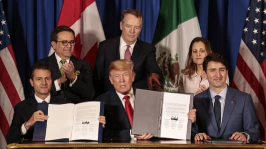 Enrique Pena Nieto, Mexico's president, from front left, U.S. president Donald Trump, and Justin Trudeau, Canada's prime minister, sit for photographs as Ildefonso Guajardo Villarreal, Mexico's secretary of economy, from back left, Robert Lighthizer, U.S. trade representative, and Chrystia Freeland, Canada's minister of foreign affairs, stand after signing the United States-Mexico-Canada Agreement (USMCA) at the G-20 Leaders' Summit in Buenos Aires, Argentina, on Friday Nov. 30, 2018.