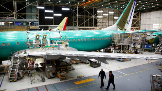 Two workers walk under the wing of a 737 Max aircraft at the Boeing factory in Renton, Washington, March 27, 2019.