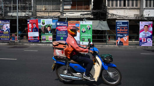 A motorist rides past electoral posters in Bangkok, Thailand on the eve of the March 24, 2019 general election.