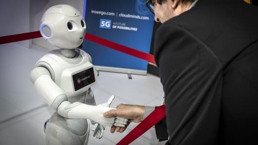 The humanoid robot Pepper of the American company CloudMinds is seen shaking hands with a visitor during the MWC2019.