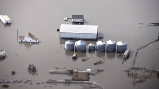 This Monday, March 18, 2019 file photo shows flooding and storage bins under water on a farm along the Missouri River in rural Iowa north of Omaha, Neb.
