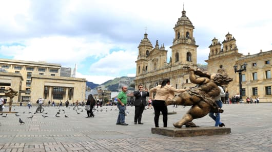 Tourists inspect bronze sculptures depicting happy and chubby women, by Chinese artist Xu Hongfei at the Bolivar Square in Bogota, Colombia, on 8 November 2017.